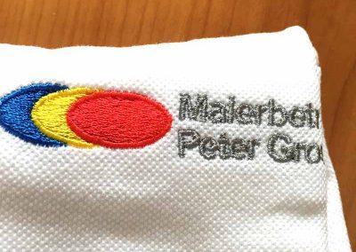 """Stickerei eines Logos auf einem weißen Poloshirt. Drei Farben und der Schriftzug """"Malerbetrieb"""""""